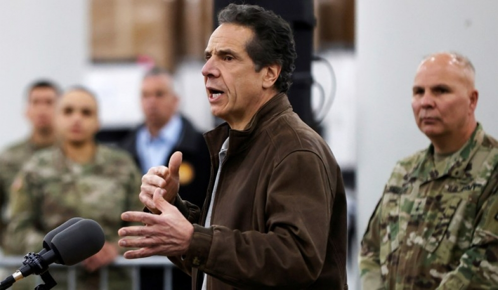 New York Governor Andrew Cuomo speaks to the media as U.S. Army personnel look at the Jacob K. Javits Convention Center in Manhattan, which will be partially converted into a hospital for patients affected by the coronavirus outbreak, March 23, 2020. (Mike Segar/Reuters)